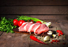 Raw juicy meat steaks ready for roasting on a black chalk board. Stock Images