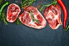 Raw juicy meat steaks ready for roasting and vegatables on a black board background. Space for text royalty free stock photo