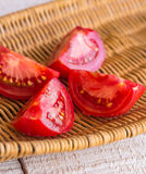 Raw juicy red tomato quarters in a wicker basket Royalty Free Stock Photos