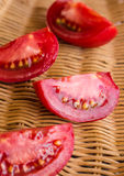 Raw juicy red tomato quarters in a wicker basket Royalty Free Stock Images