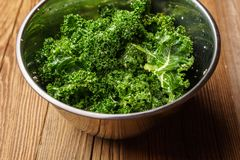 Raw kale chips in a bowl - angled view royalty free stock image