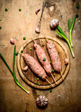 Raw kebab of beef with garlic and onions. On a wooden table Royalty Free Stock Images