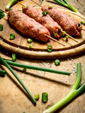 Raw kebab with green onions on the Board. On a wooden table Stock Image