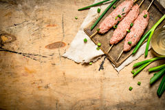 Raw kebab with green onions on the Board. On a wooden table Royalty Free Stock Images