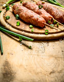Raw kebab with green onions on the Board. On a wooden table Royalty Free Stock Photo