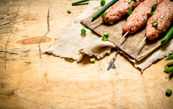 Raw kebab with green onions on the Board. On a wooden table Stock Photography