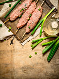 Raw kebab with green onions on the Board. On a wooden table Stock Images
