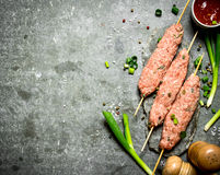 Raw kebab with green onions and tomato sauce. On the stone table Royalty Free Stock Images
