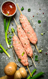 Raw kebab with green onions and tomato sauce. On the stone table Stock Photos
