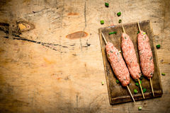 Raw kebab pork on Board. On a wooden table Royalty Free Stock Images