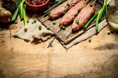 Raw kebab with tomato sauce and green onions. On a wooden table Royalty Free Stock Photos