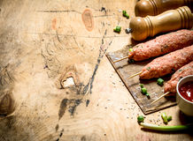 Raw kebab with tomato sauce and green onions. On a wooden table Royalty Free Stock Image