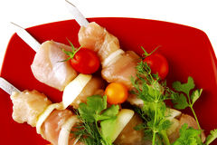 Raw kebabs on red plate Royalty Free Stock Photography