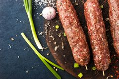 Raw kebabs  with seasoning , onion and garlic on the wooden board Stock Image