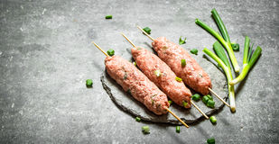 Raw kebabs on Wooden skewers with green onions. On the stone table Stock Photography