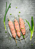 Raw kebabs on Wooden skewers with green onions. On the stone table Stock Image