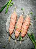 Raw kebabs on Wooden skewers with green onions. On the stone table Royalty Free Stock Image