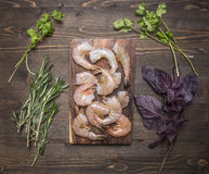 Raw king prawns with herbs on a cutting board on wooden rustic background top view close up. Raw king prawns herbs on a cutting board on wooden rustic background Royalty Free Stock Photography