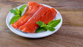 Raw King Salmon. Raw wild king Salmon Fillet lying on white place, on wooden background, decorated with mint leaves Stock Photography
