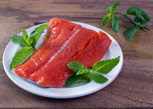 Raw King Salmon. Raw wild king Salmon Fillet lying on white place, on wooden background, decorated with mint leaves Royalty Free Stock Photo