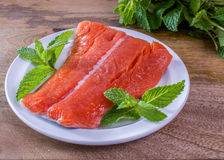 Raw King Salmon. Raw wild king Salmon Fillet lying on white place, on wooden background, decorated with mint leaves and a bunch of mint in the back Stock Photo