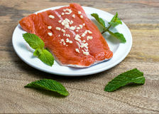 Raw King Salmon. Raw wild king Salmon Fillet lying on white place, on wooden background, decorated with mint leaves and garlic marinate Stock Image