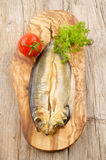 Raw kipper on a wooden board. Kipper with fresh tomato and parsley on wooden board Stock Images