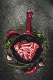 Raw lamb or beef ribs. Raw fresh meat, uncooked lamb or beef ribs with hot pepper, garlic and spices in frying pan skillet on dark stone background, copy space Stock Photos
