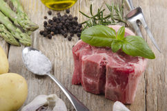 Raw lamb chop with basil on rustic wooden table Royalty Free Stock Photo