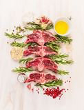 Raw lamb  chop cutlet with oil , rosemary and garlic on white wooden background. Top view Royalty Free Stock Photography