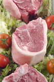Raw lamb chop with tomato and salad Royalty Free Stock Images