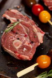 Raw Lamb Chops. With cherry tomato and rosemary herb ready to cook. Selective focus Stock Photo