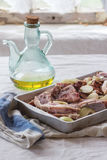 Raw lamb chops marinated. Marinating of raw lamb chops with onion, olive oil and pepper in old aluminum baking dish over kitchen table with white tablecloth Stock Photos