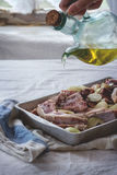 Raw lamb chops marinated. Woman's hand pouring olive oil at marinated raw lamb chops with onion and pepper in old aluminum baking dish. Over kitchen table with Royalty Free Stock Photography