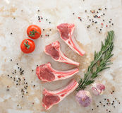 Raw lamb chops. Rack of Lamb with rosemary,  young garlic and spices on marble background, top view Royalty Free Stock Images