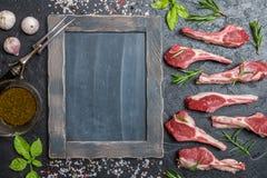 Raw lamb chops with salt, pepper, rosemary stock photo