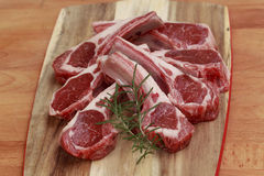 Raw lamb cutlets with rosemary. On chopping board Royalty Free Stock Photo