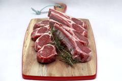 Raw lamb cutlets with rosemary. On chopping board white background Royalty Free Stock Photos