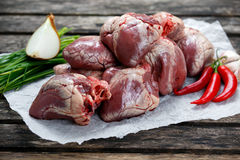 Raw Lamb Hearts on crumpled paper, decorated with vegetables. on Stock Photography