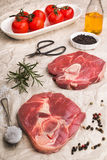 Raw lamb leg chops on brown paper. Raw lamb leg chops with coarse salt, peppercorn, rosemary, olive oil and fresh tomato on brown paper Royalty Free Stock Photography