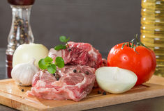 Raw lamb leg chops on a wooden chopping board. With garlic, onion, pepper, tomato and vegetable oil Royalty Free Stock Images