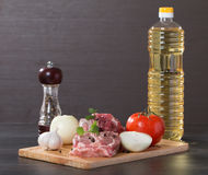 Raw lamb leg chops on a wooden chopping board. With garlic, onion, pepper, tomato and vegetable oil Stock Photos