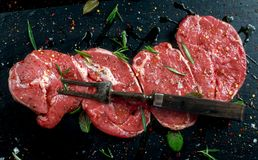 Raw Lamb leg steaks on stone chopping board with vintage fork served with sea salt and chillie flakes, rosemary and mint Stock Photos