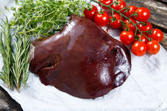 Raw Lamb liver on crumpled paper,  decorated with greens and vegetables. on old  wooden table Royalty Free Stock Photos