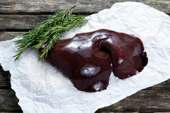 Raw Lamb liver on crumpled paper, decorated with Rosemary. on old  wooden table Stock Photos