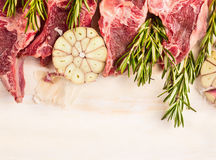 Raw lamb meat with garlic and rosemary on white wooden backgound, top view Royalty Free Stock Photos