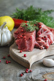 Raw lamb meat with spices on wood board over old wooden backgrou Royalty Free Stock Photography