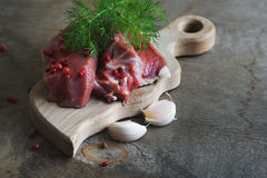Raw lamb meat with spices on wood board over old wooden backgrou Royalty Free Stock Image