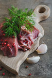 Raw lamb meat with spices on wood board over old wooden backgrou Royalty Free Stock Photos
