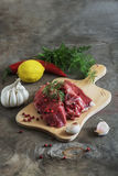 Raw lamb meat with spices on wood board over old wooden backgrou Stock Photo
